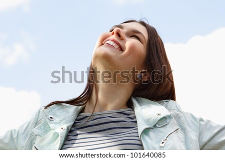 Happy smiling young attractive woman over clean blue sky - stock photo