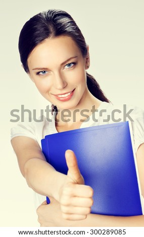 Happy smiling young beautiful businesswoman showing thumbs up gesture - stock photo