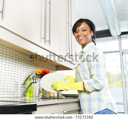 Happy smiling young black woman enjoying washing dishes in kitchen - stock photo