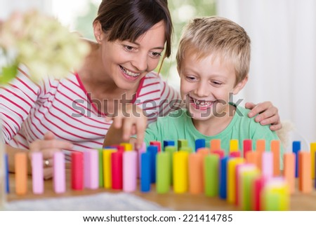 Happy smiling young boy playing with colorful building blocks helped by his loving mother with her arm around his shoulders - stock photo