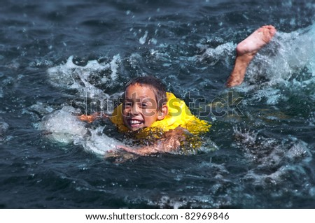happy smiling young boy swimming in the water - stock photo