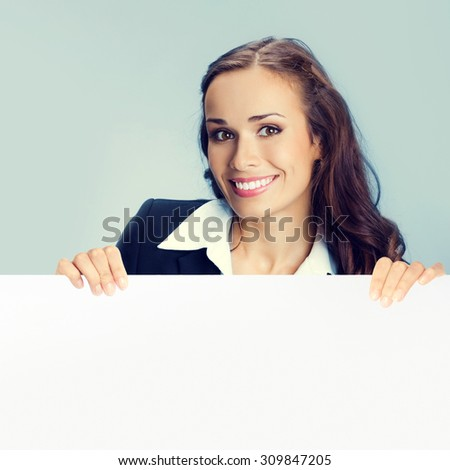 Happy smiling young brunette businesswoman showing blank signboard with copyspace area for slogan or text message - stock photo