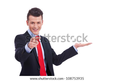 Happy smiling young business man showing blank area for sign or copyspace and pointing his finger at you, isolated over white background - stock photo