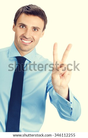 Happy smiling young business man showing two fingers or victory gesture - stock photo