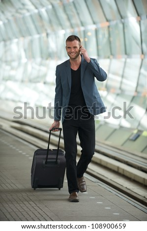 Happy smiling young business man wearing casual suit and walking in the train station with a phone and suitcase in hand - stock photo
