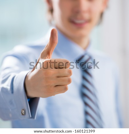 Happy smiling young business man with thumbs up gesture at his office - stock photo