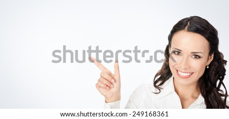 Happy smiling young business woman showing blank area for sign or copyspase, against grey background, with copyspace