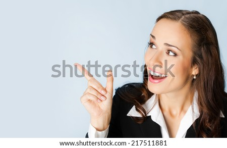 Happy smiling young business woman showing blank area for sign or copyspase, over blue background - stock photo