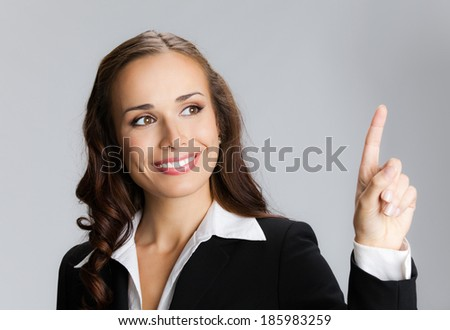 Happy smiling young business woman showing blank area for sign or copyspase, over grey background - stock photo