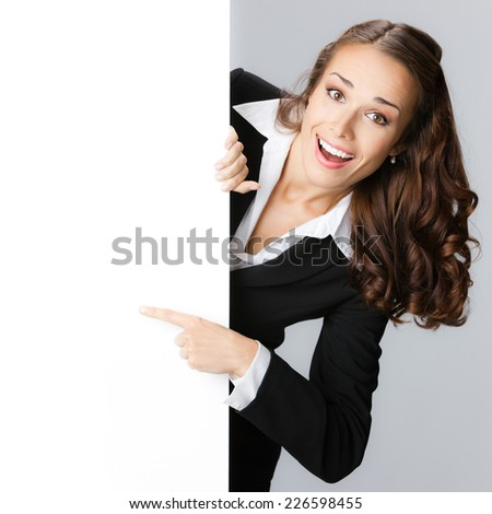 Happy smiling young business woman showing blank signboard, against grey background - stock photo