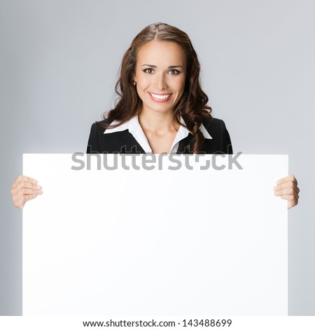 Happy smiling young business woman showing blank signboard, over gray background