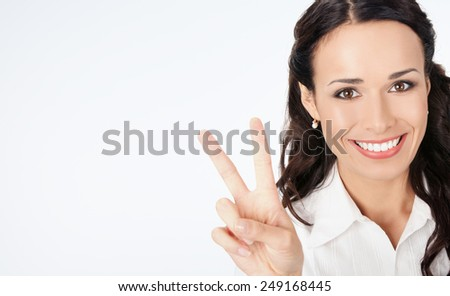Happy smiling young business woman showing four fingers, against grey background, with copyspace - stock photo