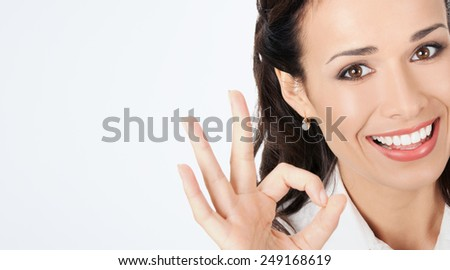 Happy smiling young business woman showing okay gesture, against grey background, with copyspace - stock photo