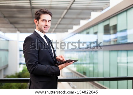Happy smiling young businessman using his digital tablet at the office - stock photo
