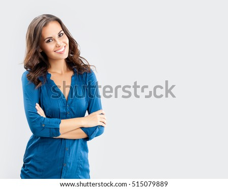 Happy smiling young businesswoman, on grey background. Caucasian brunette model in business concept studio shoot. Blank copyspace area for advertise text or slogan.