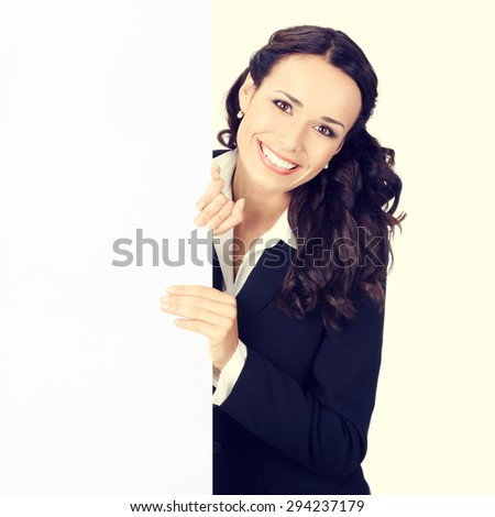 Happy smiling young businesswoman showing blank signboard