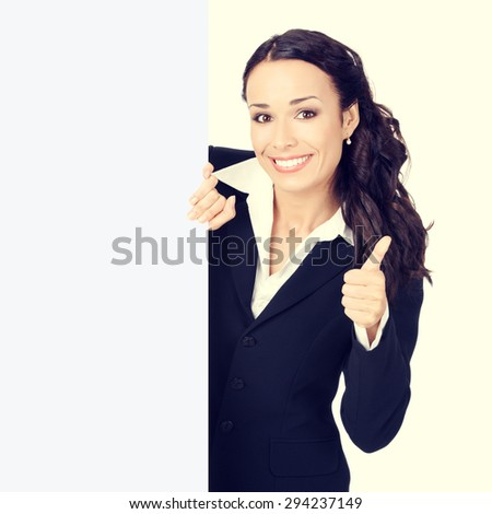 Happy smiling young businesswoman with blank signboard, showing thumb up hand sign gesture