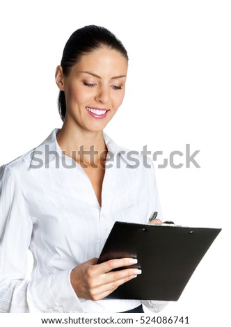 Happy smiling young businesswoman with clipboard writing, isolated on white background. Caucasian brunette female model in business success concept studio shot.