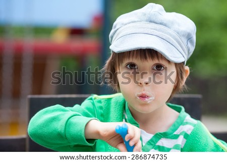 Happy smiling young child eating yogurt, outdoor, making funny faces - stock photo