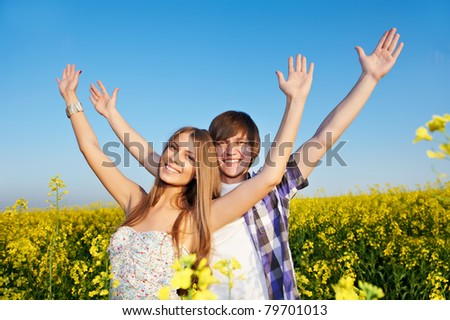 Happy smiling young couple embracing each other over yellow green rape meadow