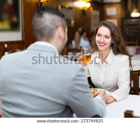 Happy smiling young couple having romantic dinner in restaurant