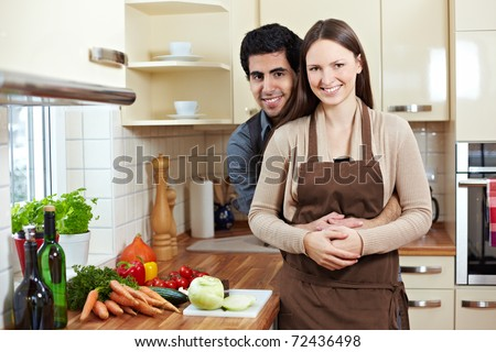 Happy smiling young couple standing in a kitchen - stock photo