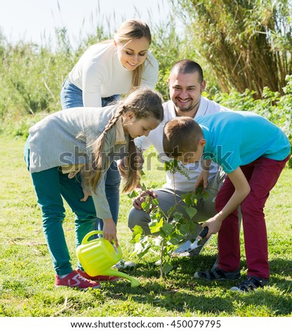 Happy smiling young couple with two kids planting a bush together