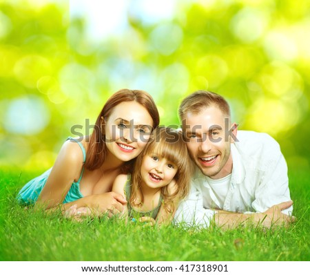 Happy smiling young family father, mother and little daughter having fun outdoors, playing together in summer park. Mom, Dad and kid laughing, lying on green grass, enjoying nature outside. Sunny day
