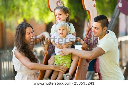 Happy smiling young family of four at children's playground in park - stock photo