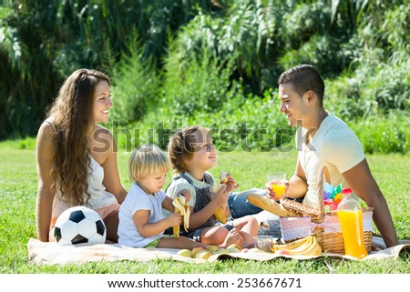 Happy smiling young family of four having picnic at meadow at summer day