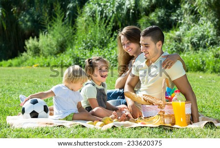 Happy smiling young family of four on picnic in park at summer day  - stock photo