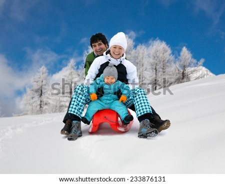 Happy smiling Young family of three sledding, having fun in Alpine mountains, ski resort, in motion  - stock photo