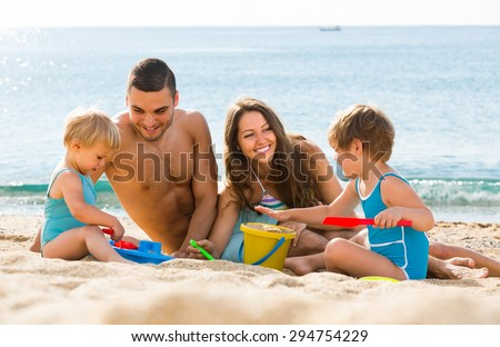 Happy smiling young family with two kids resting at beach in sunny day