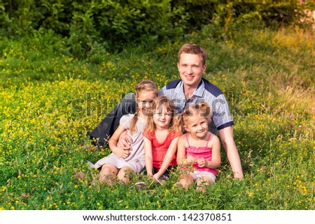 Happy smiling young father and daughters playing in the park - stock photo