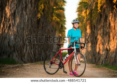 Happy smiling young female cyclist standing with bike on road with palms in sunset. Nature, healthy and active lifestyle concept
