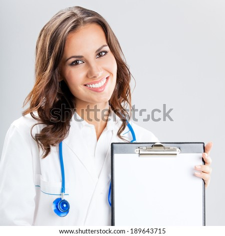 Happy smiling young female doctor showing blank clipboard with copyspace, over grey background - stock photo