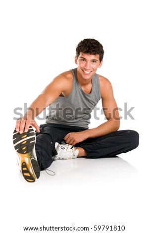 Happy smiling young fitness man sitting and making stretching exercises after gym isolated on white background - stock photo