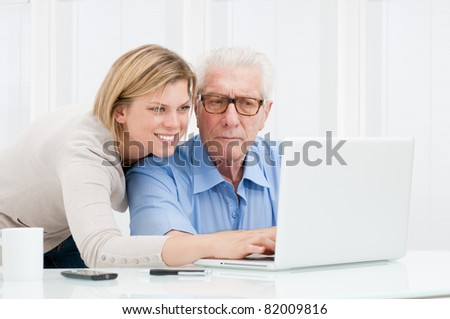 Happy smiling young girl explaining and teaching to her grandparent the use of a modern computer - stock photo