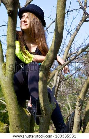 Happy smiling young girl sitting on tree with hat