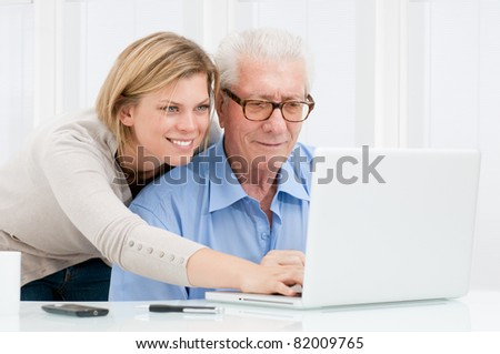 Happy smiling young girl teaching and showing new computer technology to her grandfather