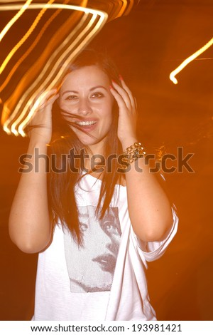Happy smiling  young girl with lightpainting, long time exposure - stock photo