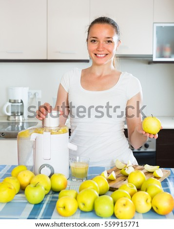 Happy smiling young housewife making fresh apple juice at kitchen