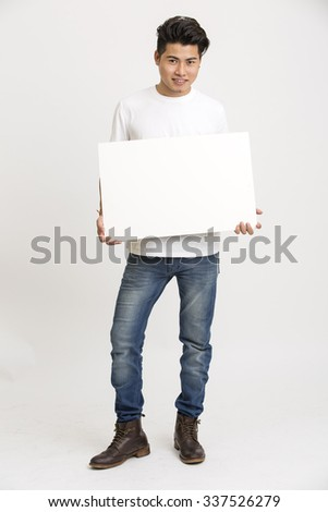Happy smiling young Indian man holding a blank billboard on white background - stock photo