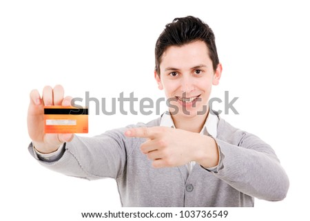Happy smiling young man holding a credit card and pointing isolated on white background - stock photo