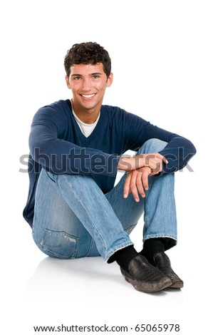 Happy smiling young man sitting on floor isolated on white background - stock photo