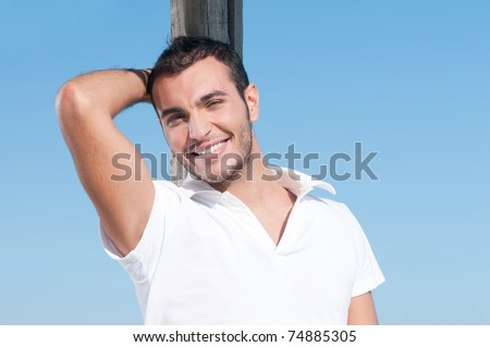 Happy smiling young man taking a break outdoor in summer - stock photo