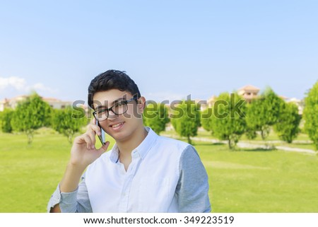 Happy smiling young man talking on mobile outdoor. - stock photo