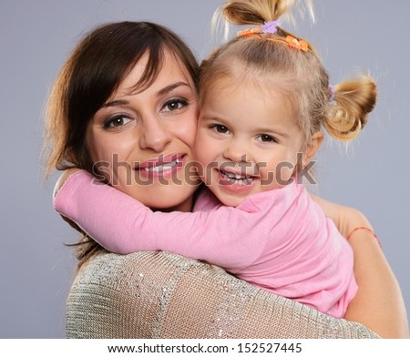Happy smiling young mother hugs her little daughter - stock photo