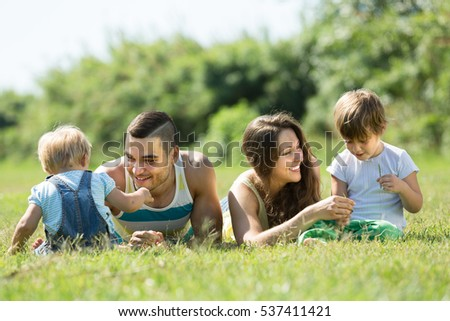 Happy smiling young parents with children in grass at park