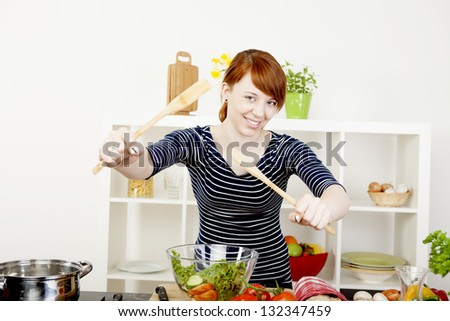 Happy smiling young redhead woman in the kitchen tossing a fresh salad with two wooden salad servers as she prepares a healthy meal - stock photo